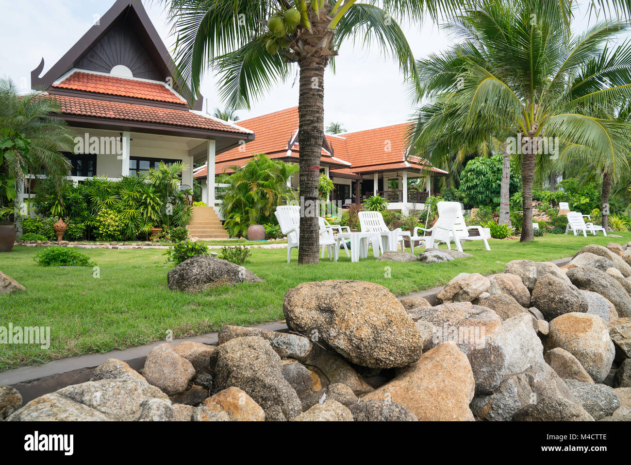 Asian architecturally designed residential properties beyond heavy rock beach wall. - Stock Image