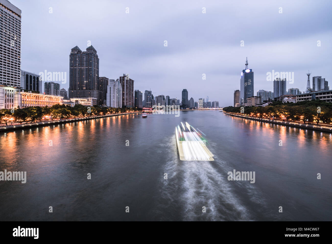 Tour boat, captured with blurred motion, sails on the Pearl river that crosses the Guangzhou downtown district in - Stock Image