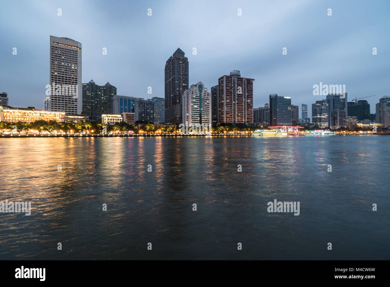 Office buildings and hotel tower reflect in the water of the Pearl river that crosses the Guangzhou downtown district - Stock Image