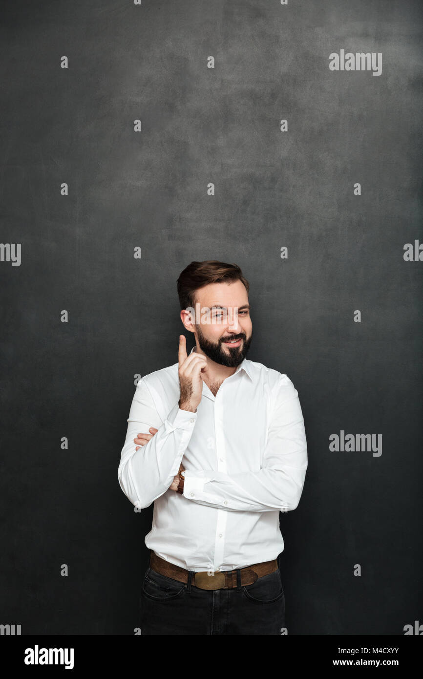 Brunette businessman posing on camera with tricky happy look pointing index finger like he know something over dark - Stock Image