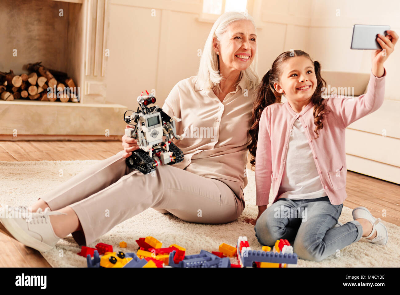 Smart little girl taking selfie with radiant grandmother - Stock Image