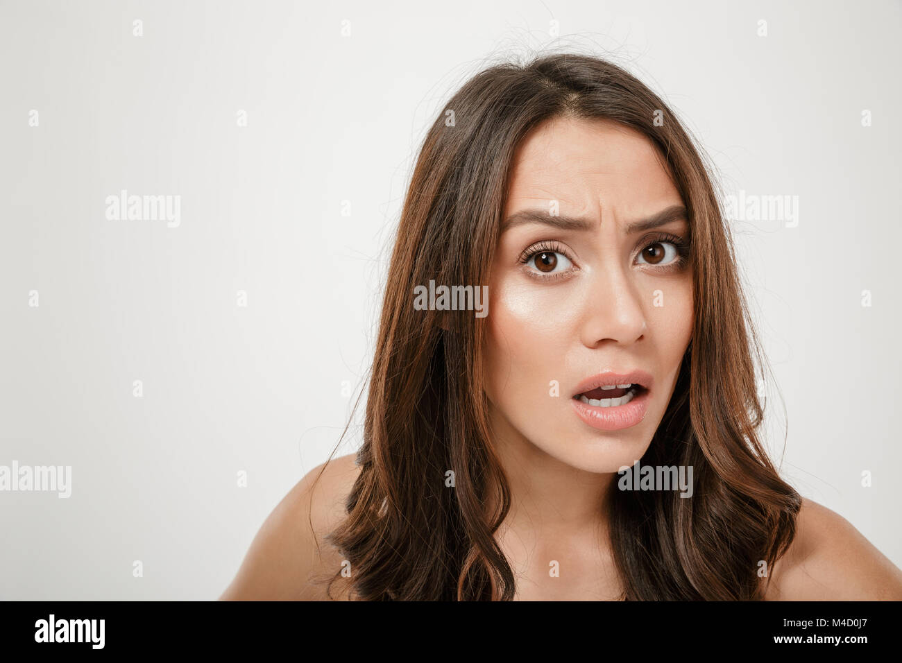 Close up portrait of confused caucasian woman looking on camera in puzzlement with facial expressions isolated over - Stock Image