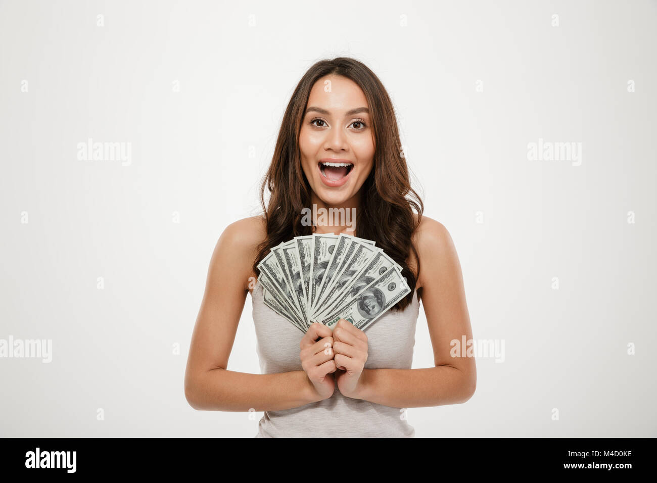 Image of gorgeous brunette female model with long hair holding fan of 100 dollar bills being rich and happy over - Stock Image