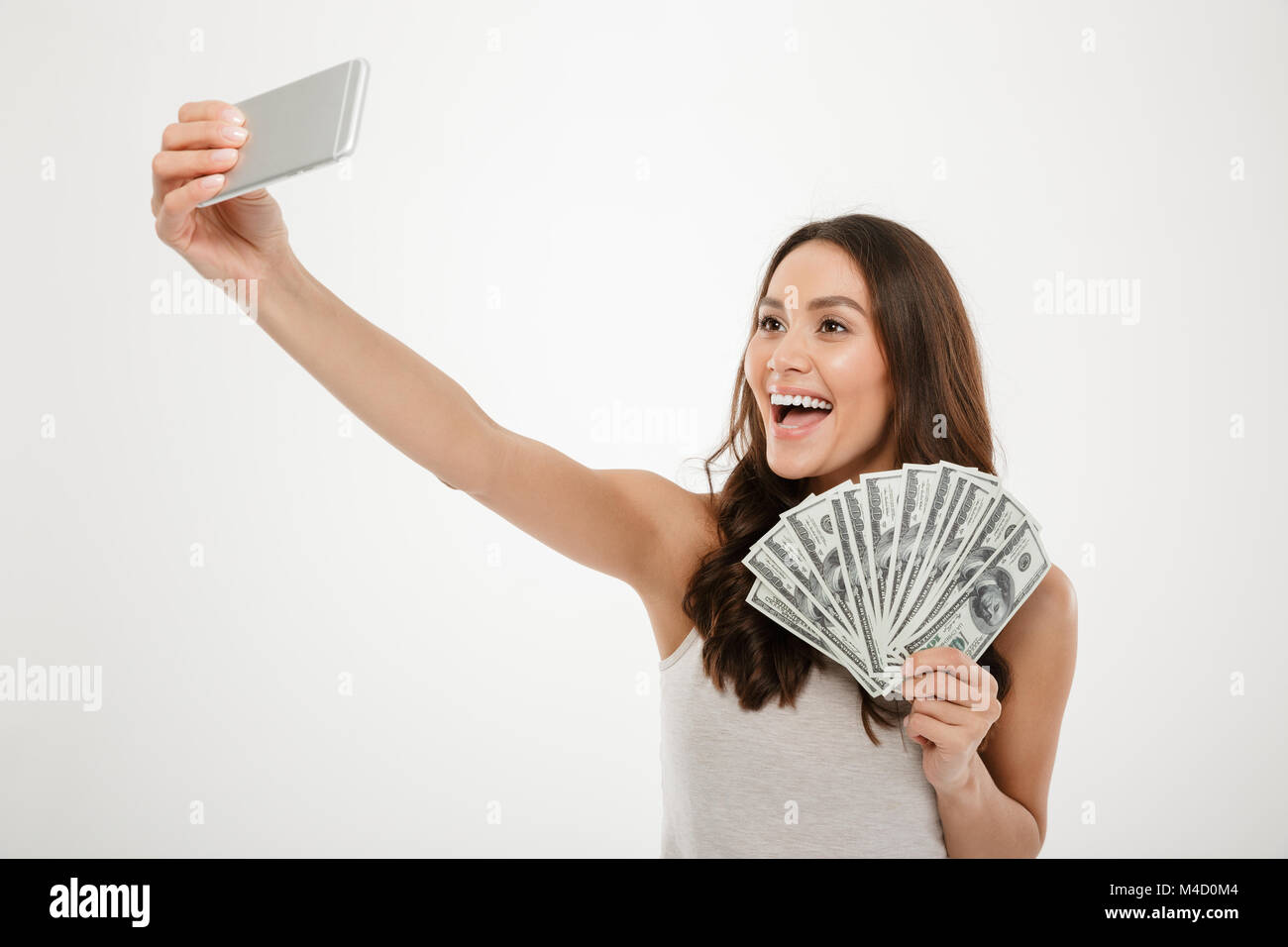 Photo of lucky rich woman making selfie on silver mobile