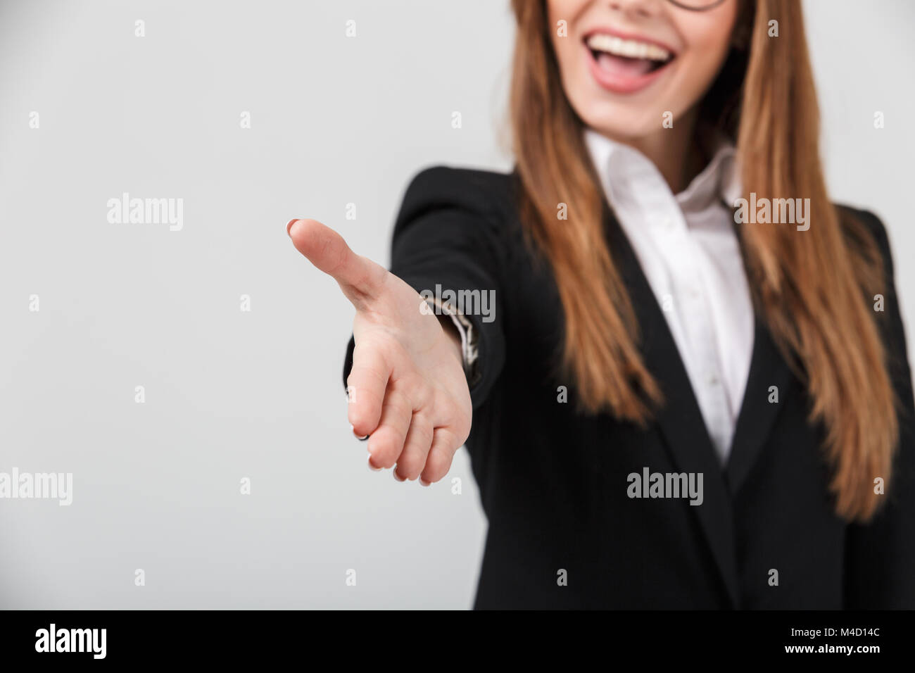 Cropped image of a happy businesswoman dressed in suit standing with outstretched hand for greeting isolated over Stock Photo