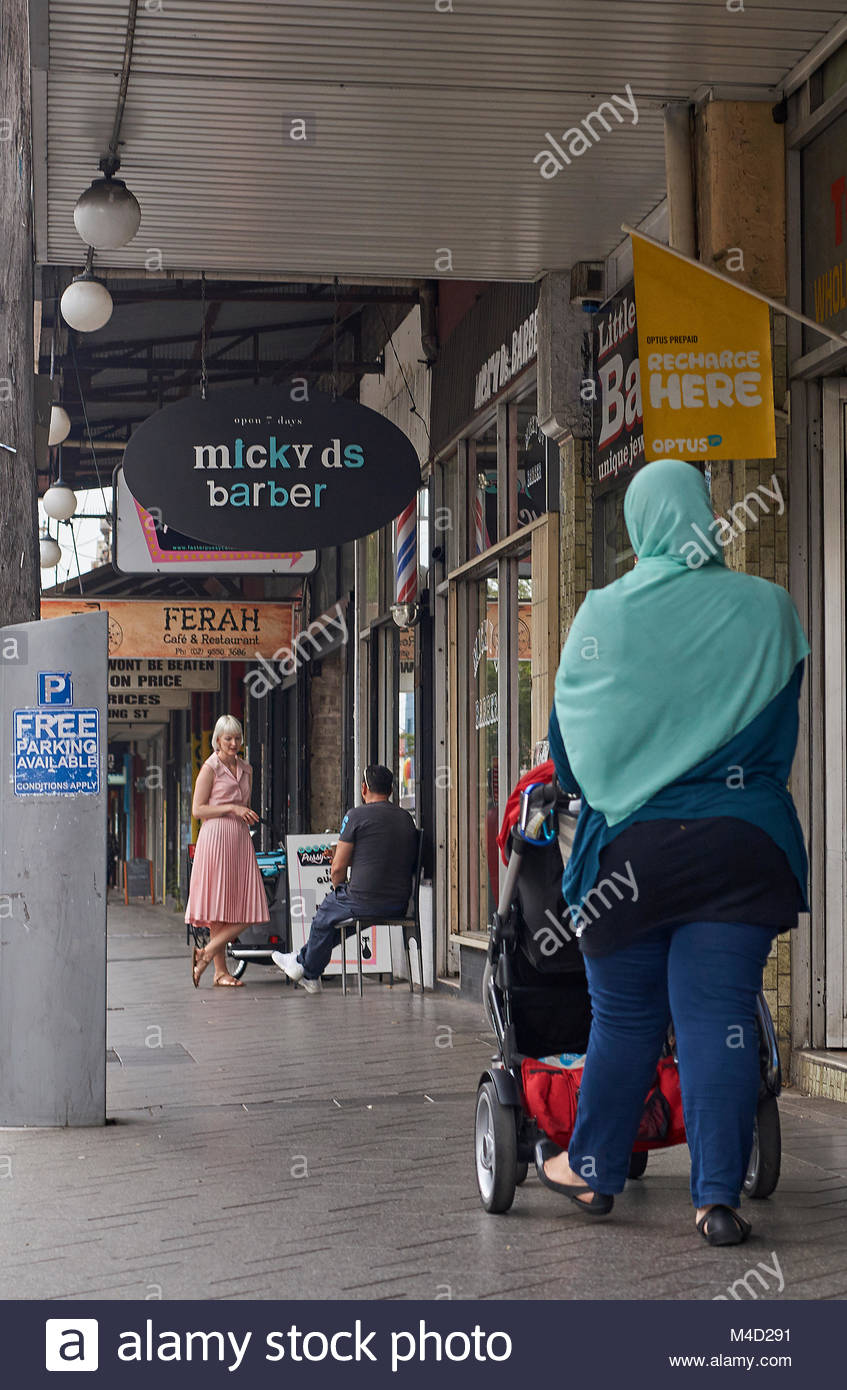 A woman wearing a burka, pushing a pram toward a lady in a retro/vintage dress on the footpath; in the inner-Sydney - Stock Image