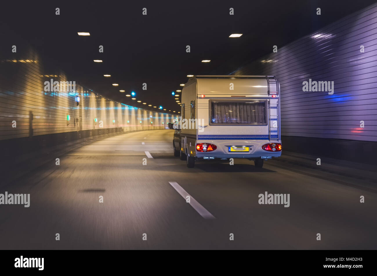 Car with residential trailer drives in a motorway tunnel. - Stock Image