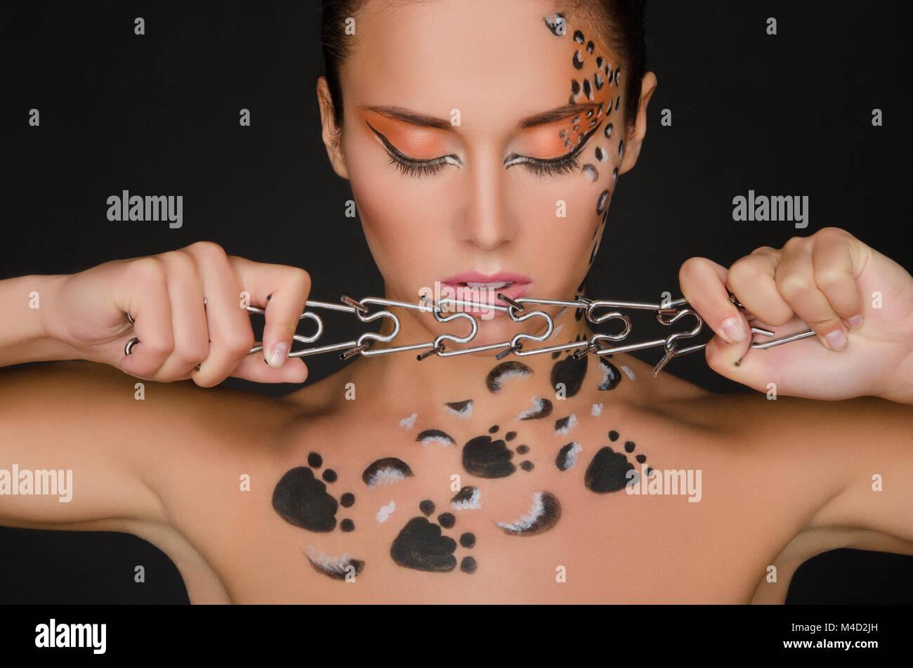 beautiful woman with animal figures keeps collar - Stock Image