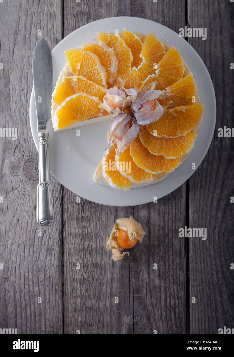 Cheesecake decorated with oranges and physalis. - Stock Image