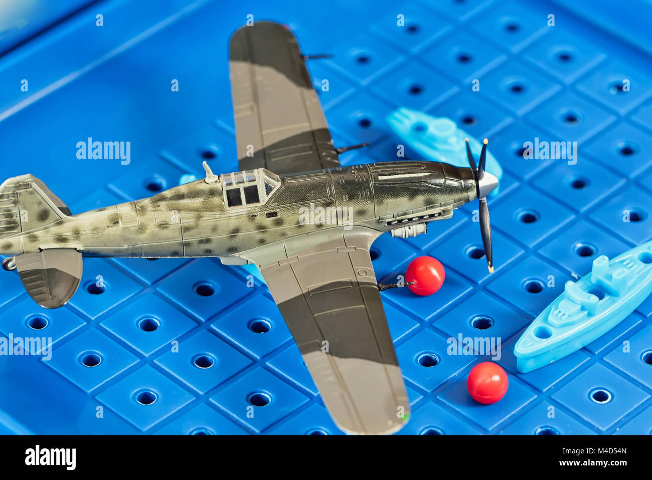 Toy military airplane is attacking toy ships - Stock Image
