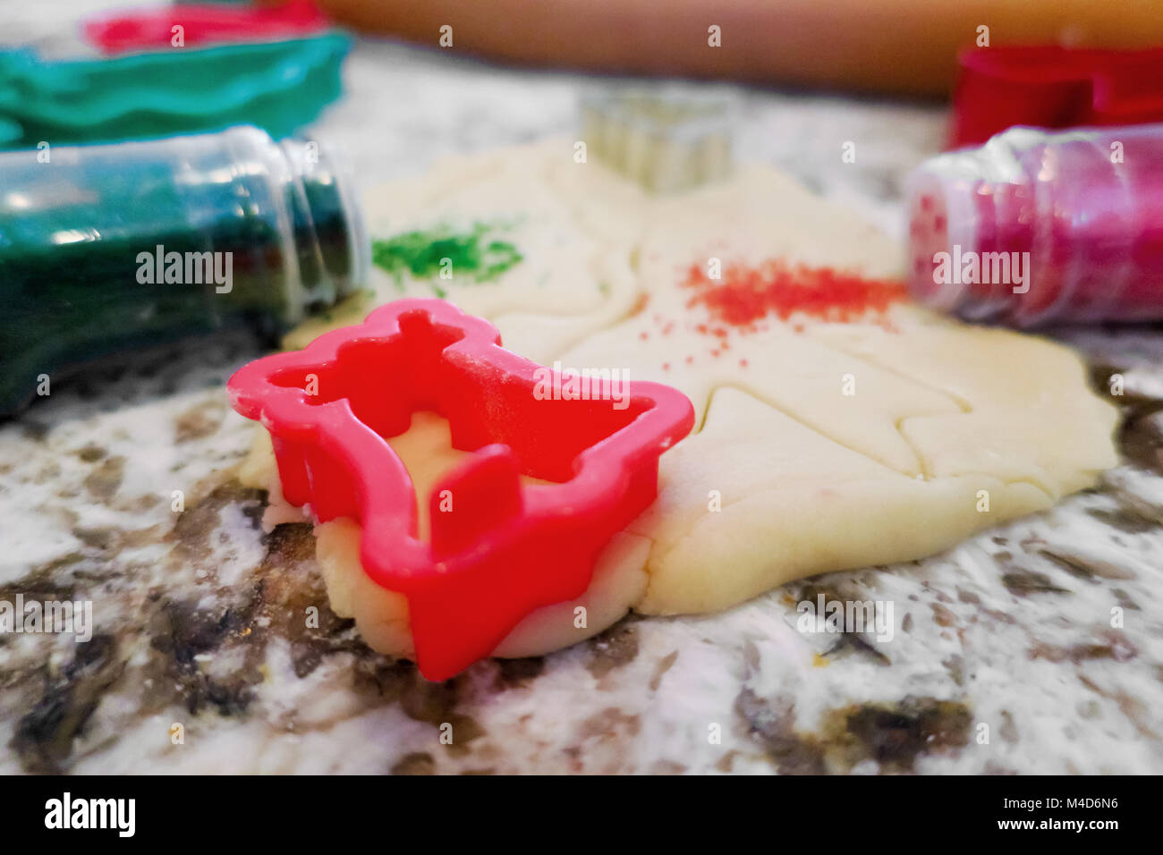 Red and green Sprinkles spilling out onto sugar cookie dough. - Stock Image