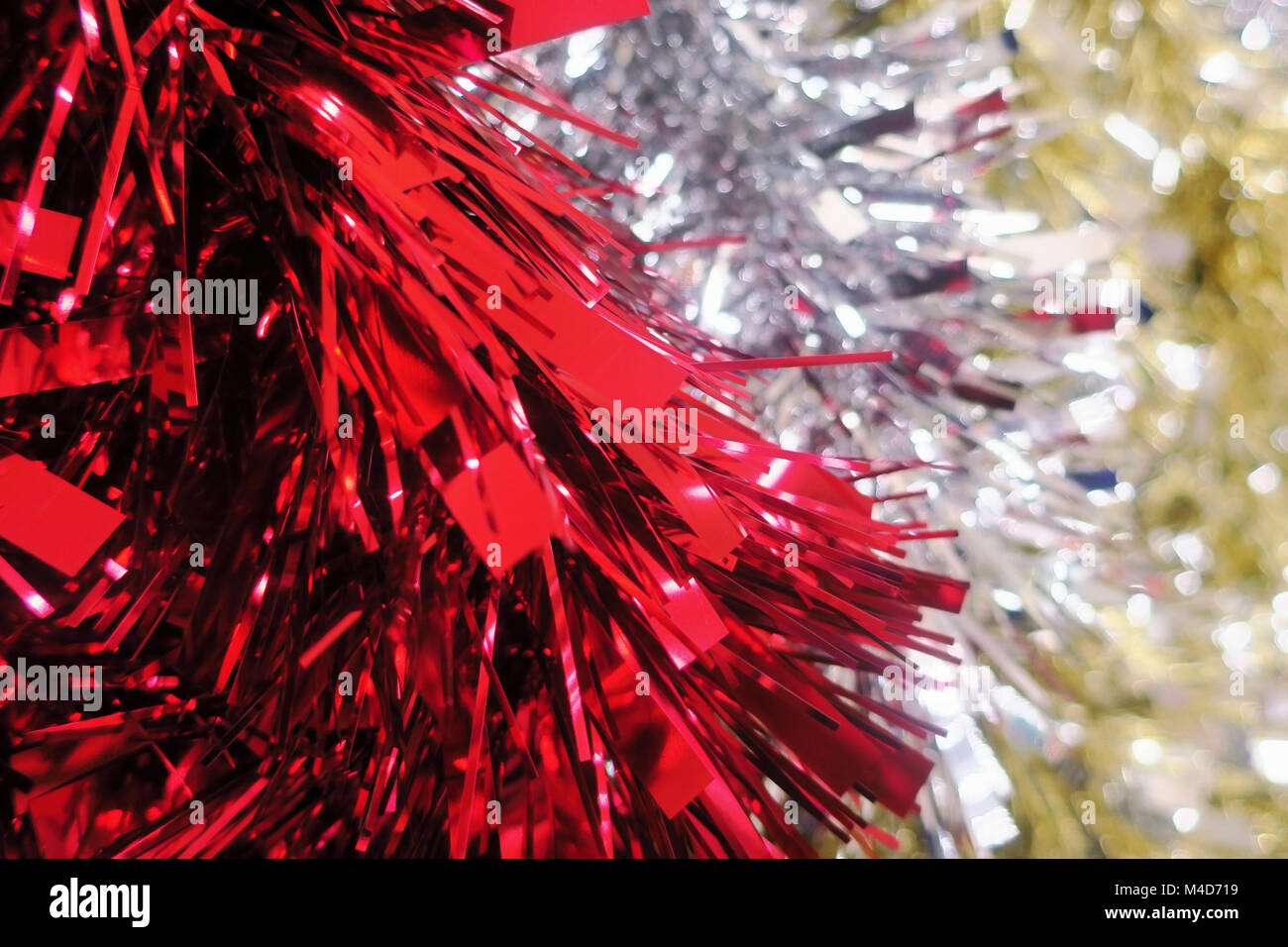 Red,silver and gold tinsel staggered. - Stock Image