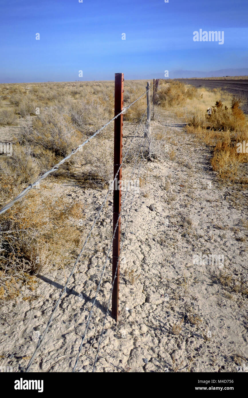 A barbed wire fence in the cracked Utah desert. - Stock Image