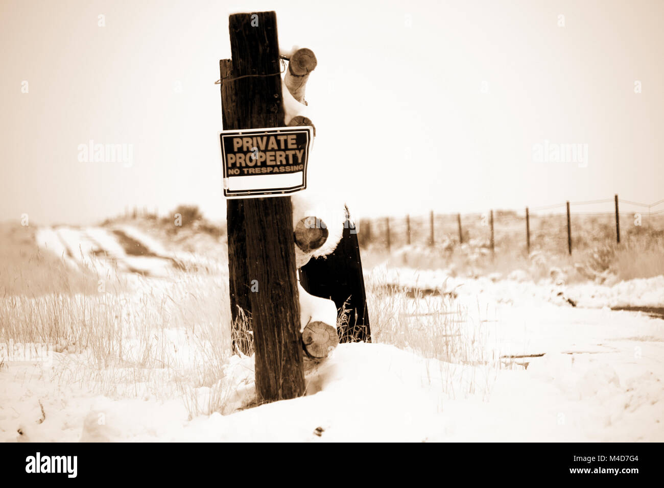 An old tire leaning up against a fence post in the Utah desert patched with snow in sepia. - Stock Image