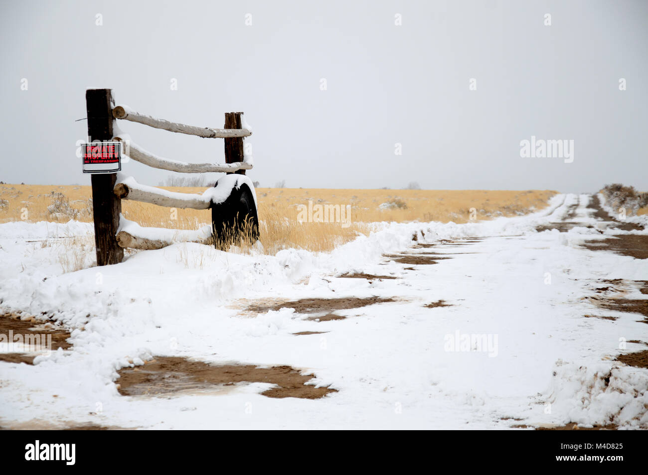 An old tire leaning up against a fence post in the Utah desert patched with snow. - Stock Image