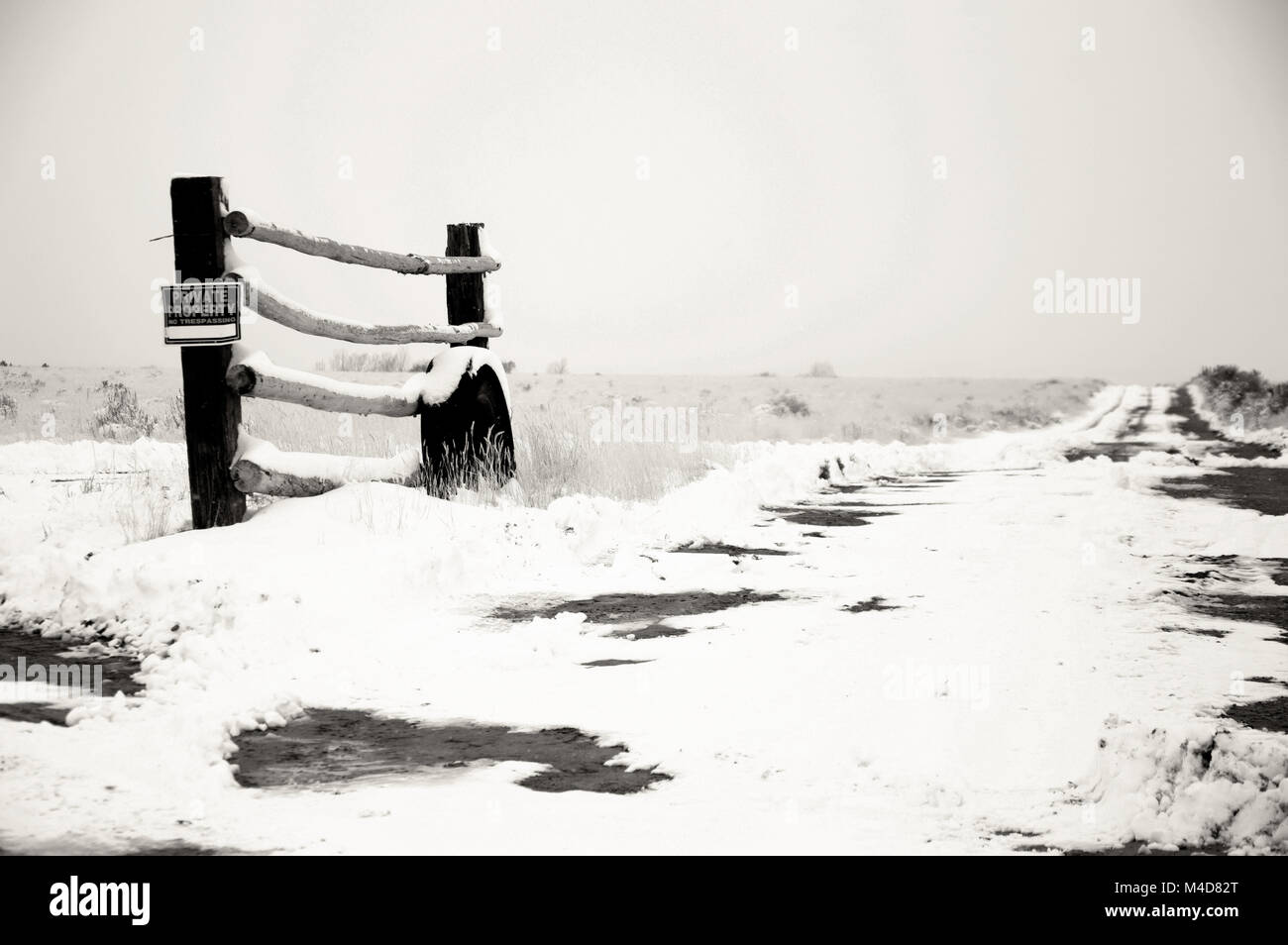 An old tire leaning up against a fence post in the Utah desert patched with snow in black and white. - Stock Image
