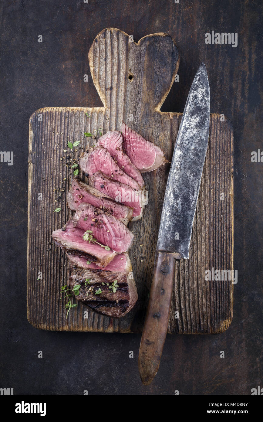 Barbecue New York Strip Steak on old wooden Baord - Stock Image