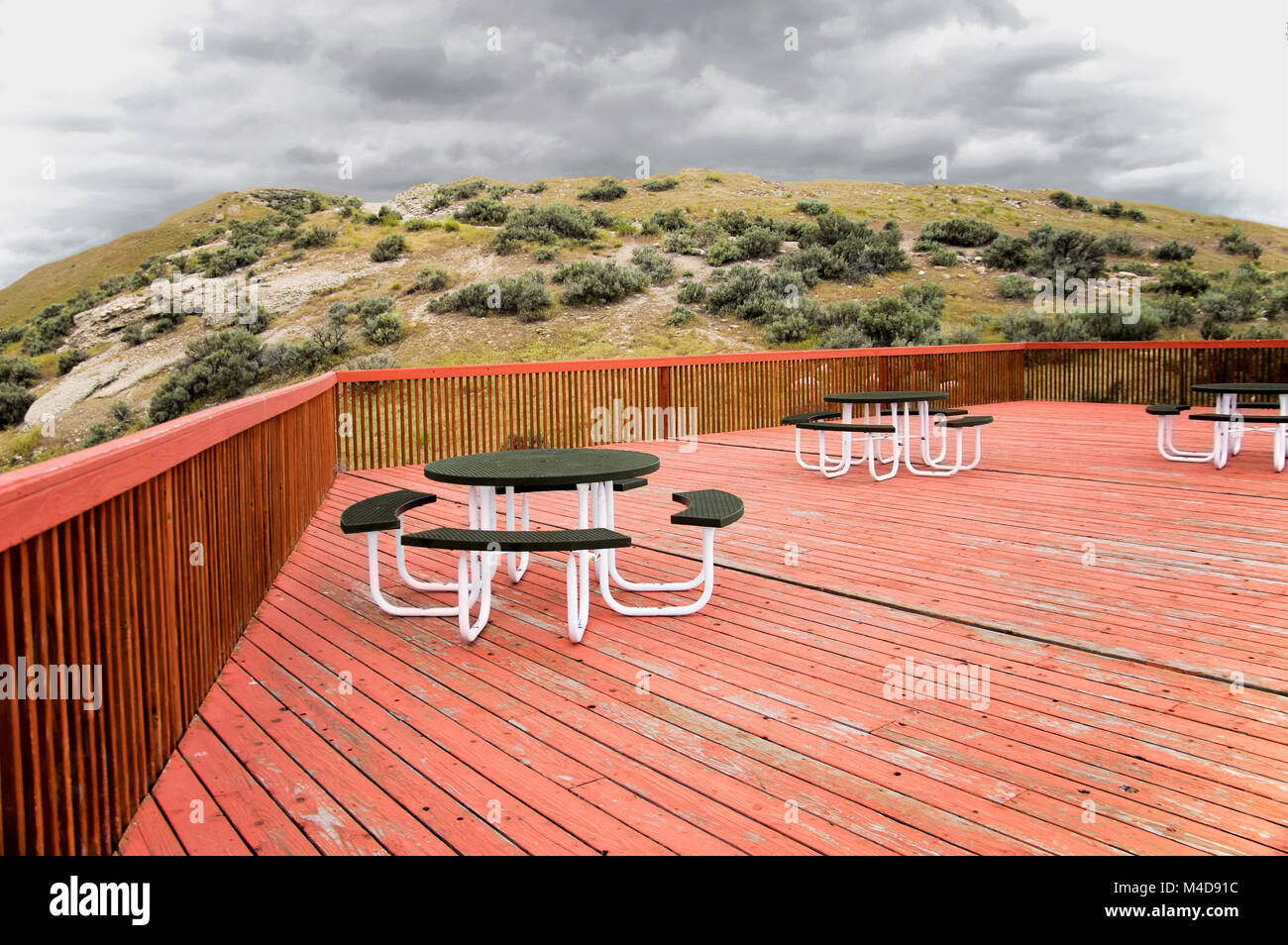 A recreation area with tables on a weathered red cedar deck looking at a desert hill with sage brush. Stock Photo