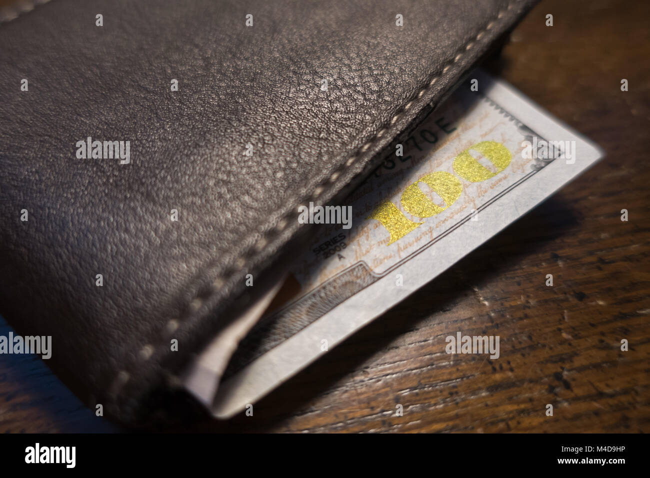 A one hundred dollar bill sticking out of a brown leather bi fold wallet. - Stock Image