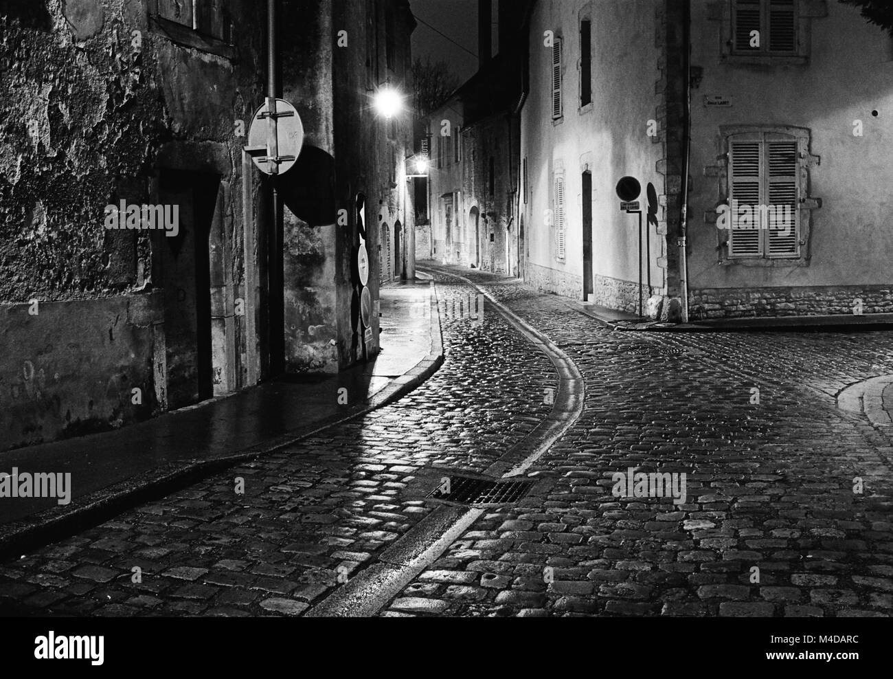 A night scene captures an empty street in the city of Beaune in France where the wet cobblestones are bright with - Stock Image