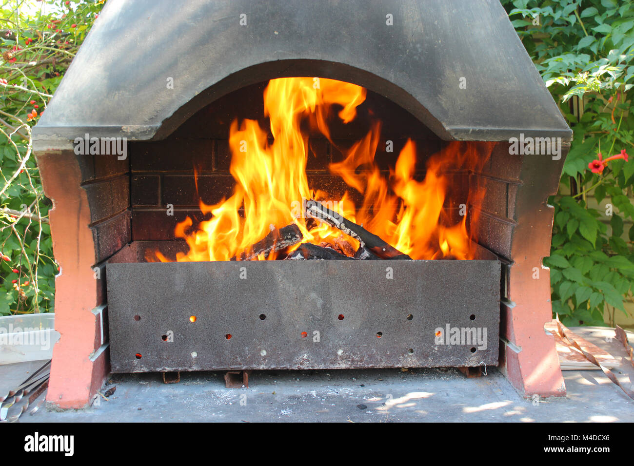 burning bright tongues of flame and brazier with shed - Stock Image