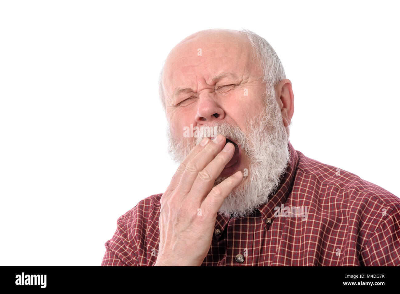 Senior man yawning, isolated on white - Stock Image