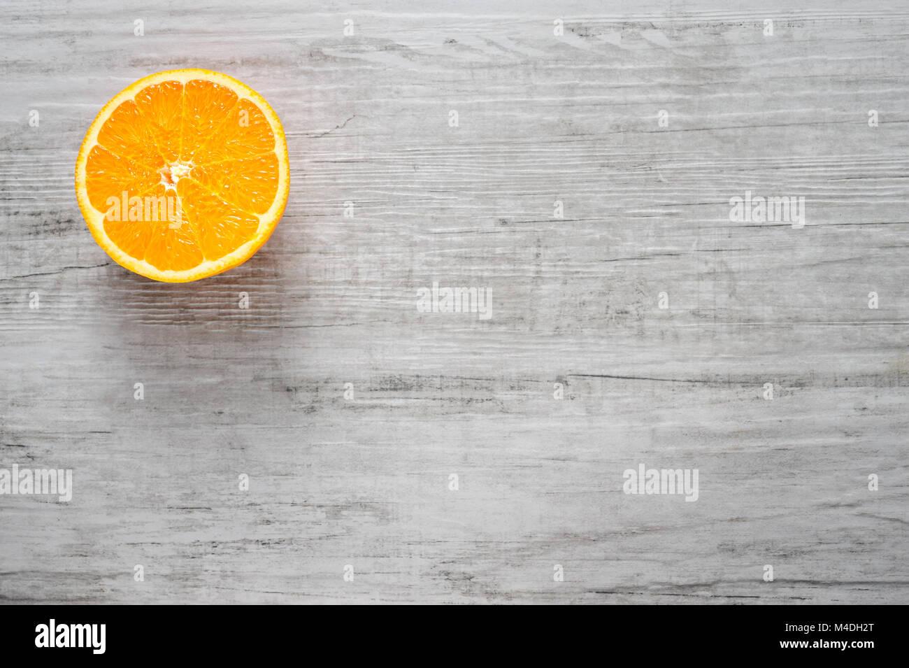 Slice of fresh oranges on white wood background - Stock Image