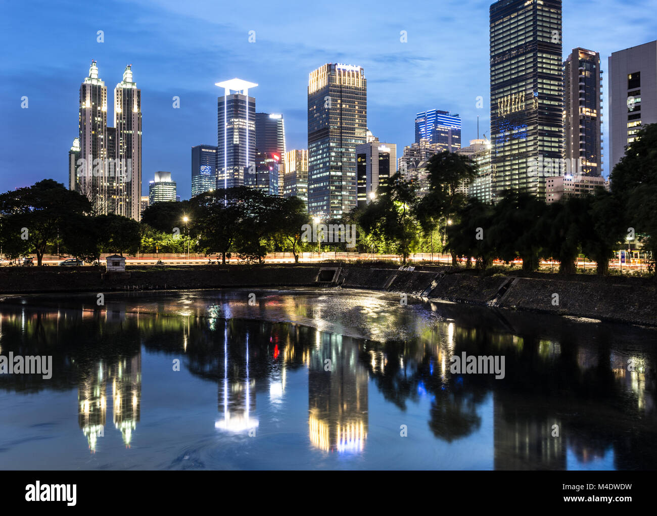Stunning reflection of office buildings and luxury apartment towers in Jakarta business district during blue hour - Stock Image
