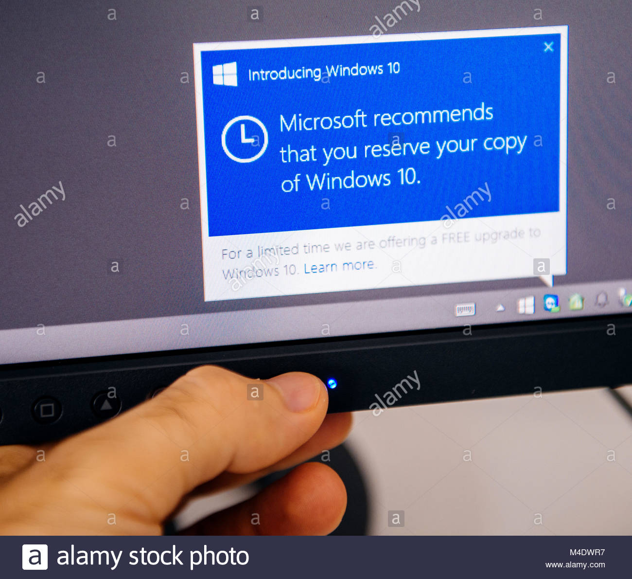Introducing Windows 10 message on computer display man touching