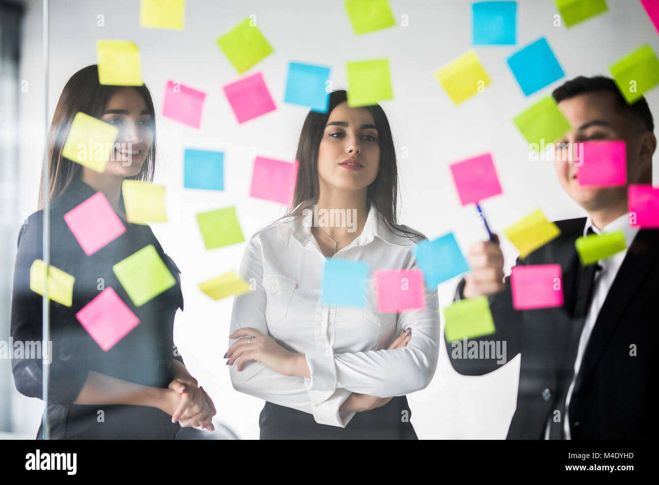 Beautiful business people are using stickers and marker, discussing ideas and smiling during the conference in office - Stock Image