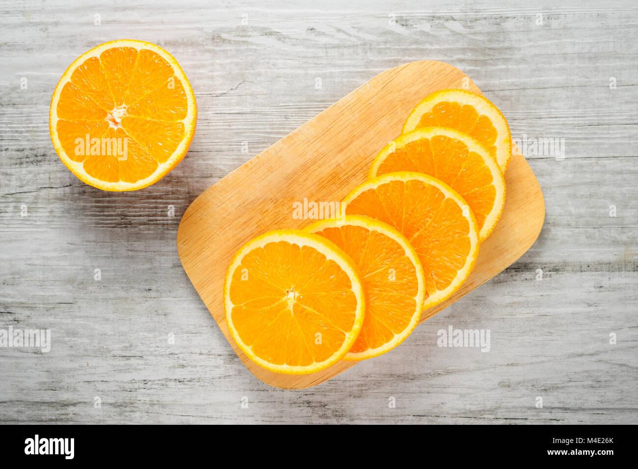 Slices of fresh oranges on white wood background - Stock Image