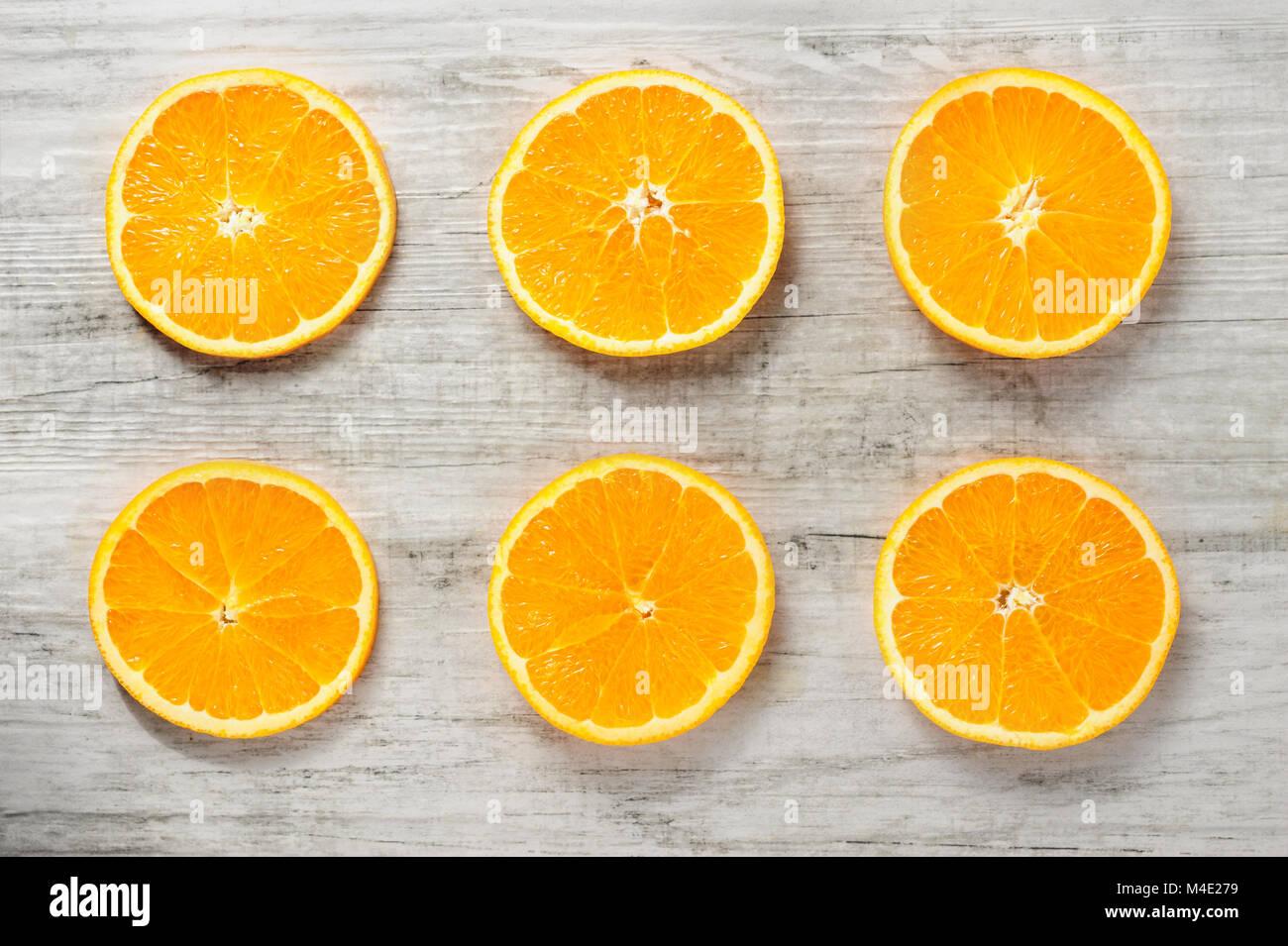 Six slices of fresh oranges on white wood background - Stock Image