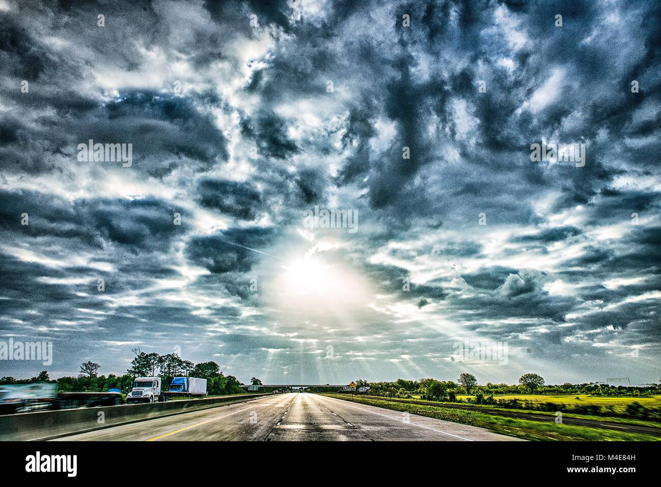 freeway through country landscape with dramatic skyes and sun rays - Stock Image