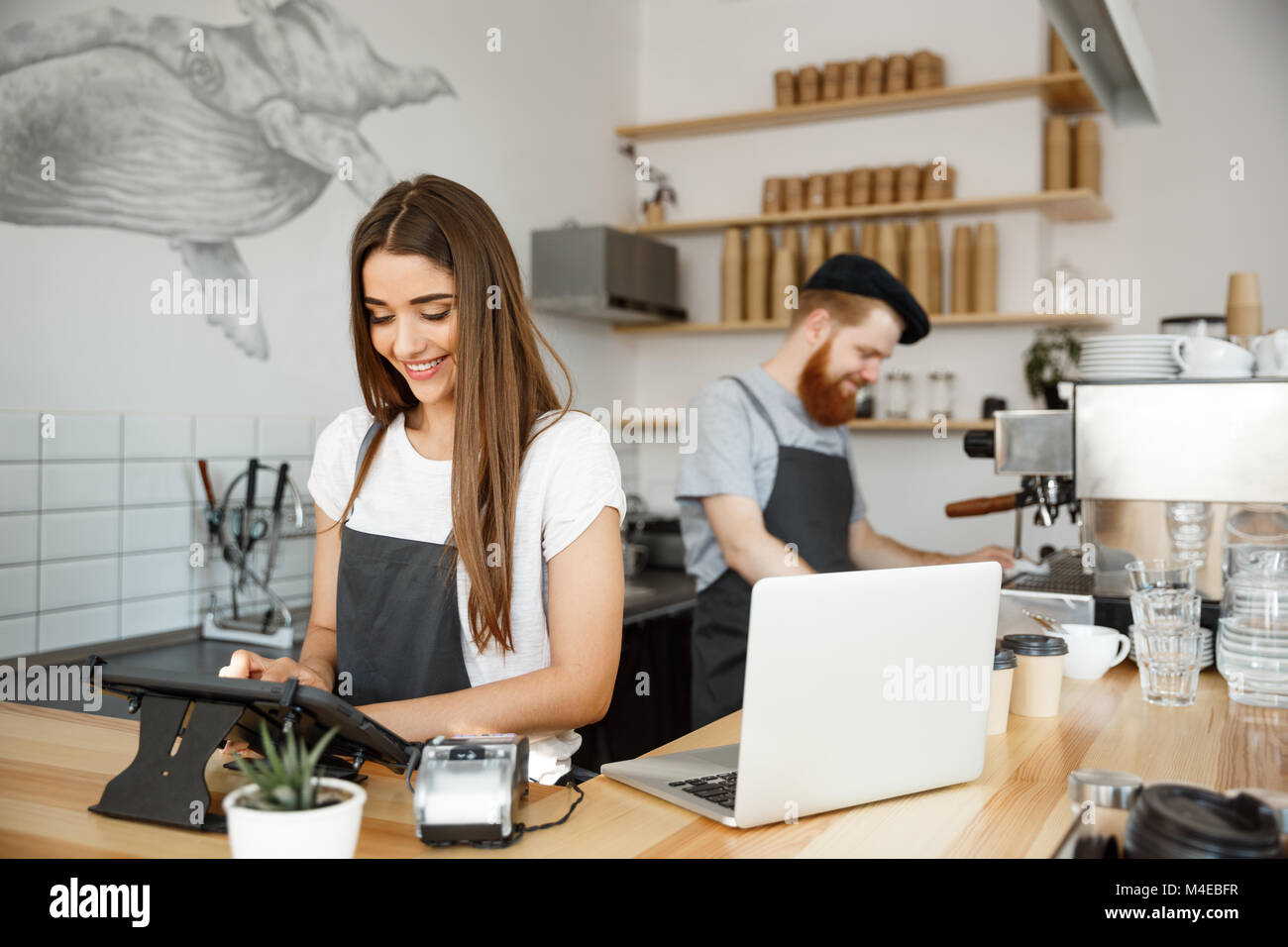 Coffee Business Concept - beautiful caucasian bartender barista or manager Posting order in digital tablet menu - Stock Image
