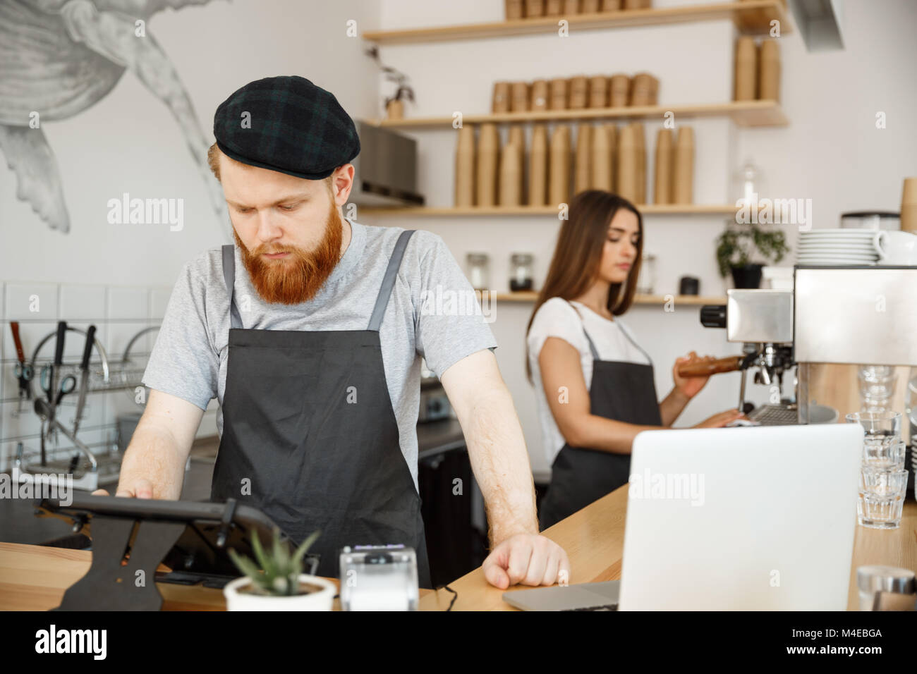 Coffee Business Concept - Young handsome bearded bartende, barista or manager posting the order from guest in digital - Stock Image