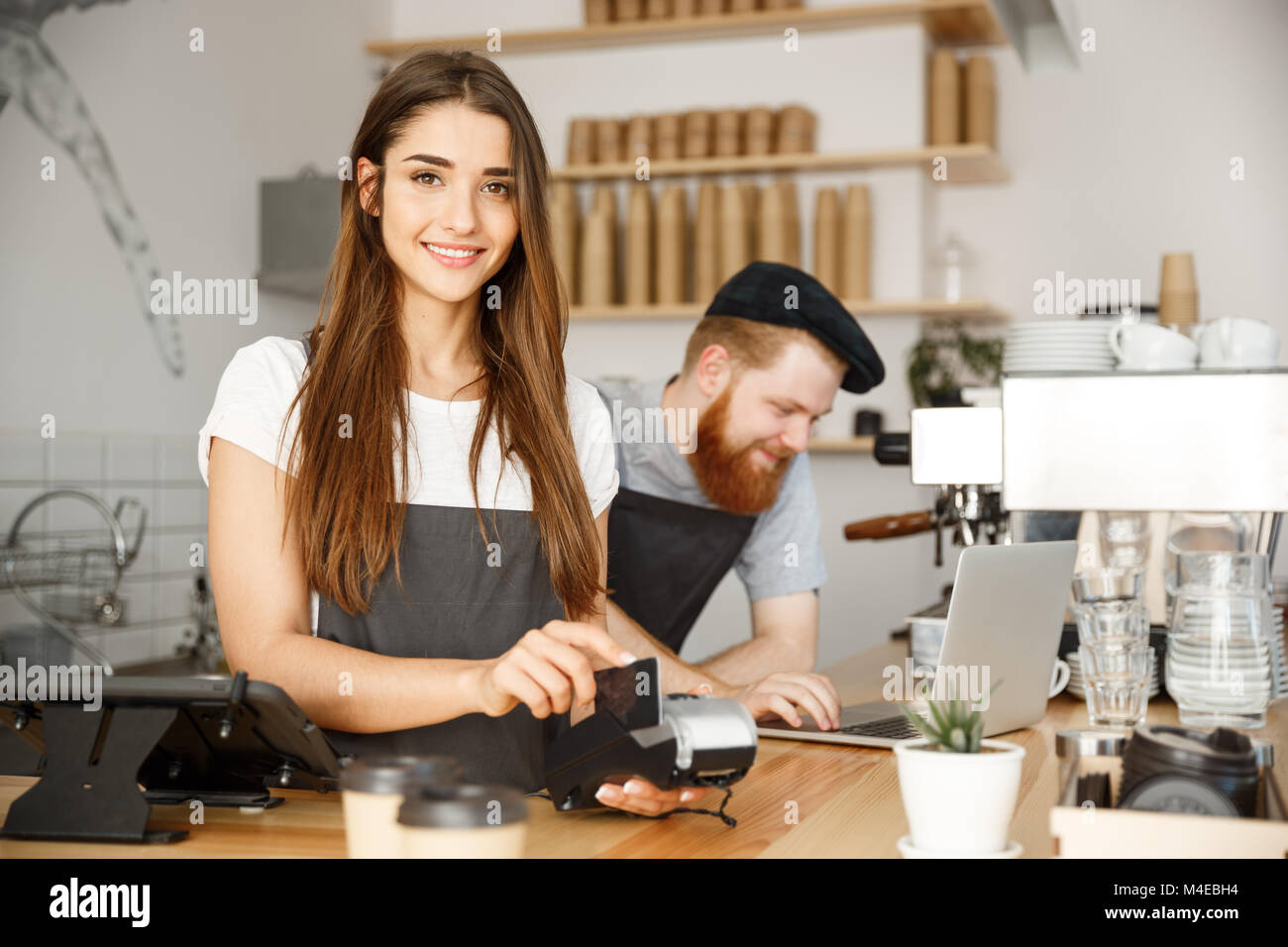 Coffee Business Concept - Beautiful female barista giving payment service for customer with credit card and smiling Stock Photo