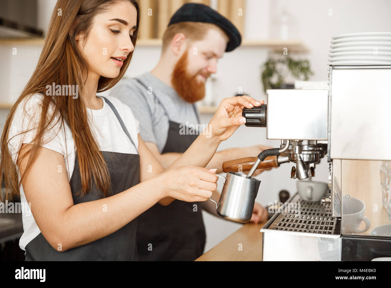 Coffee Business Concept - portrait of lady barista in apron preparing and steaming milk for coffee order with her - Stock Image