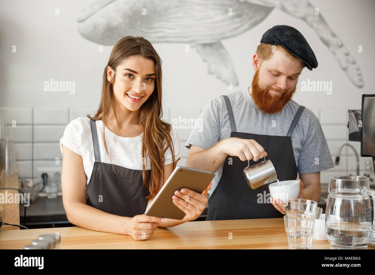 Coffee Business Concept - happy young couple business owners of small coffee shop working and planing on tablet. - Stock Image