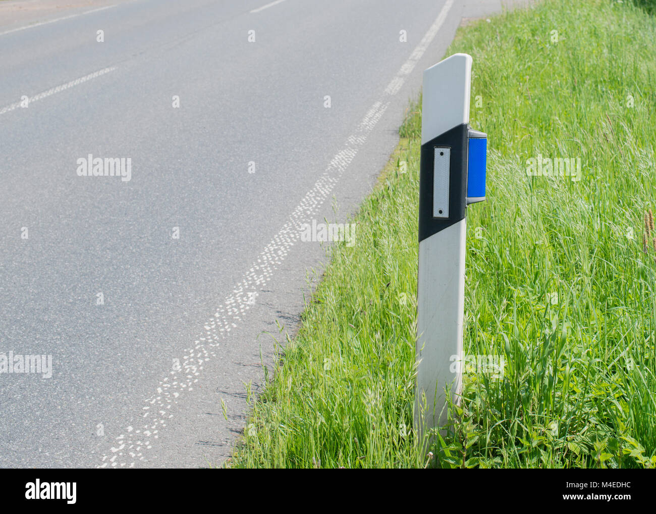 Guiding post with blue wild reflector on the road - Stock Image