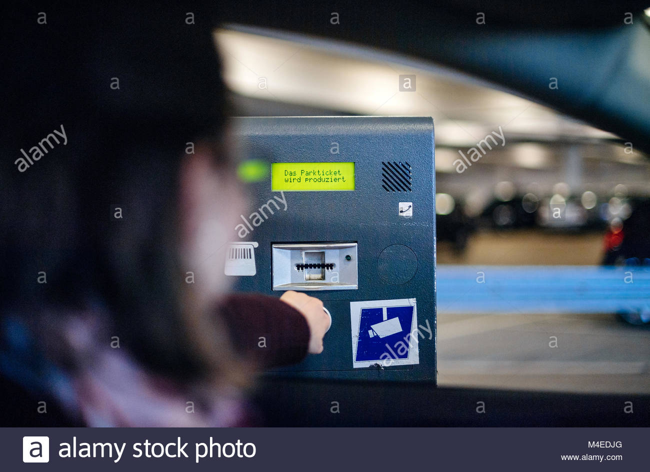 Woman paying ticket parking time space digital display - Stock Image
