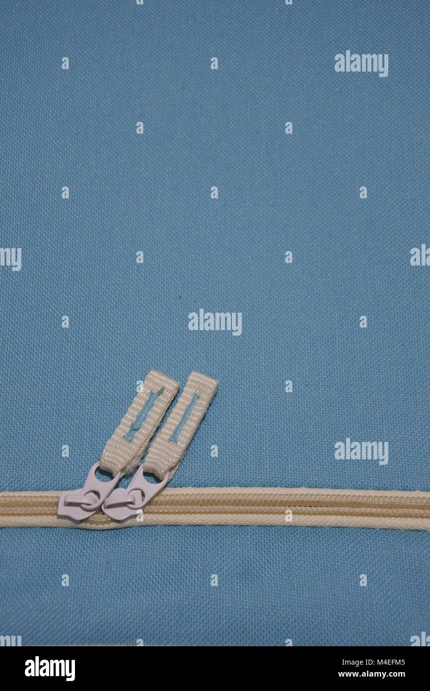Zippers inclined to the right with light blue background - Stock Image
