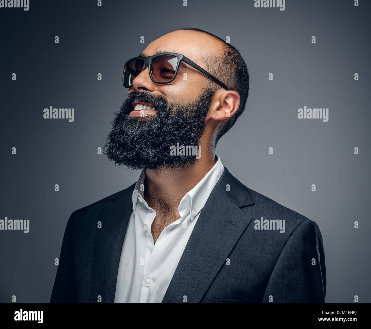 e765aca99d17 Portrait of a fashionable bearded male in a suit and sunglasses isolated on grey  background.