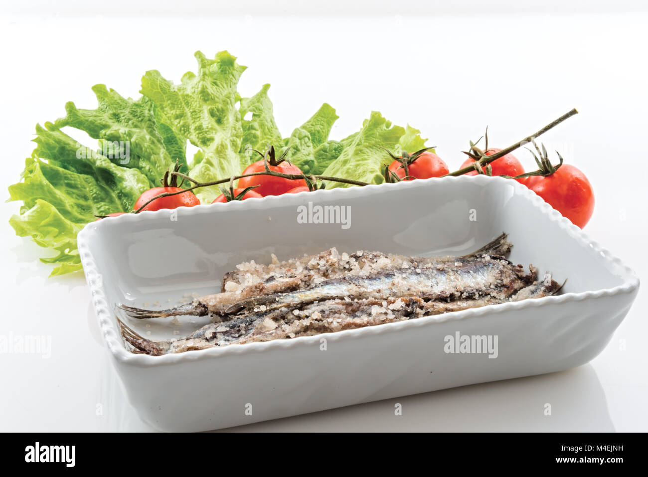 sardines salted anchovies in white pot with salad and cherry tomatoes - Stock Image