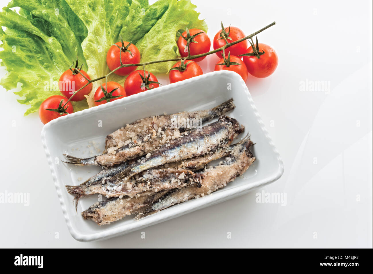 sardines salted anchovies in white pot with salad and cherry tomatoes 2 - Stock Image