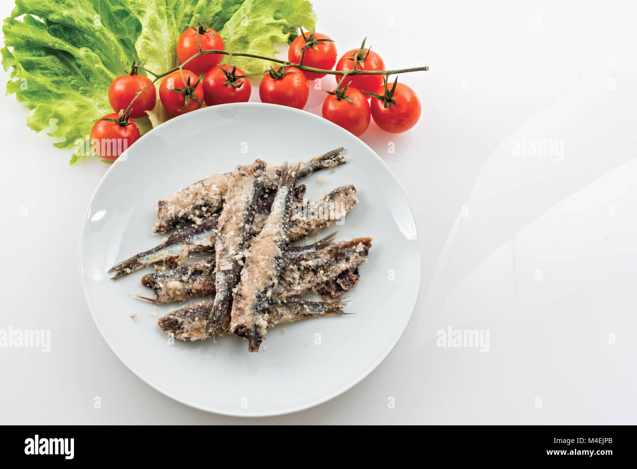 sardines salted anchovies in white plate with salad and cherry tomatoes - Stock Image