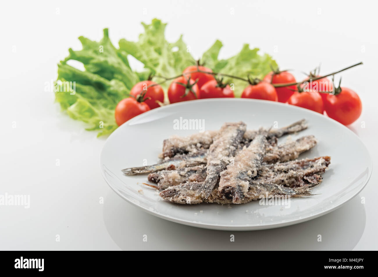 sardines salted anchovies in white plate with salad and cherry tomatoes 2 - Stock Image
