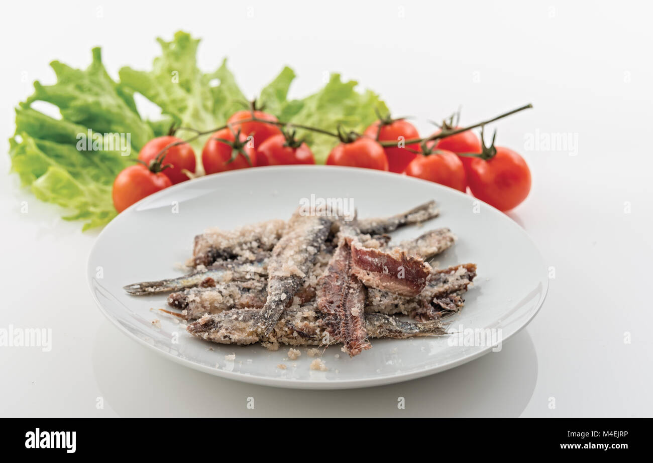 sardines salted anchovies in white plate with salad and cherry tomatoes 3 - Stock Image