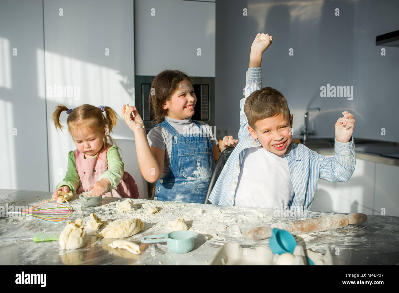 Three children prepare something from the dough. Two sisters and a brother are sitting at the kitchen table. There - Stock Image