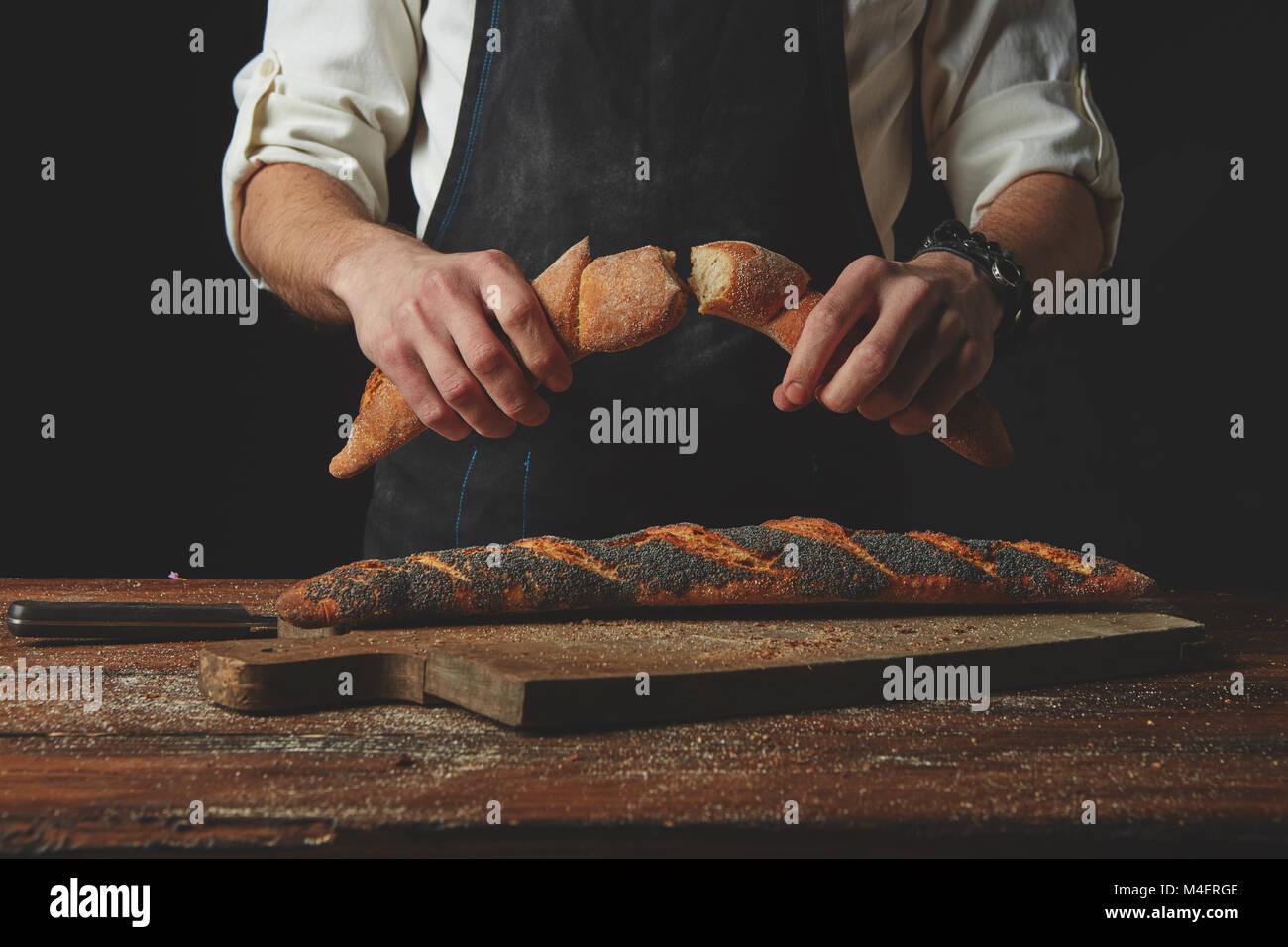 Hand breaks baguette - Stock Image