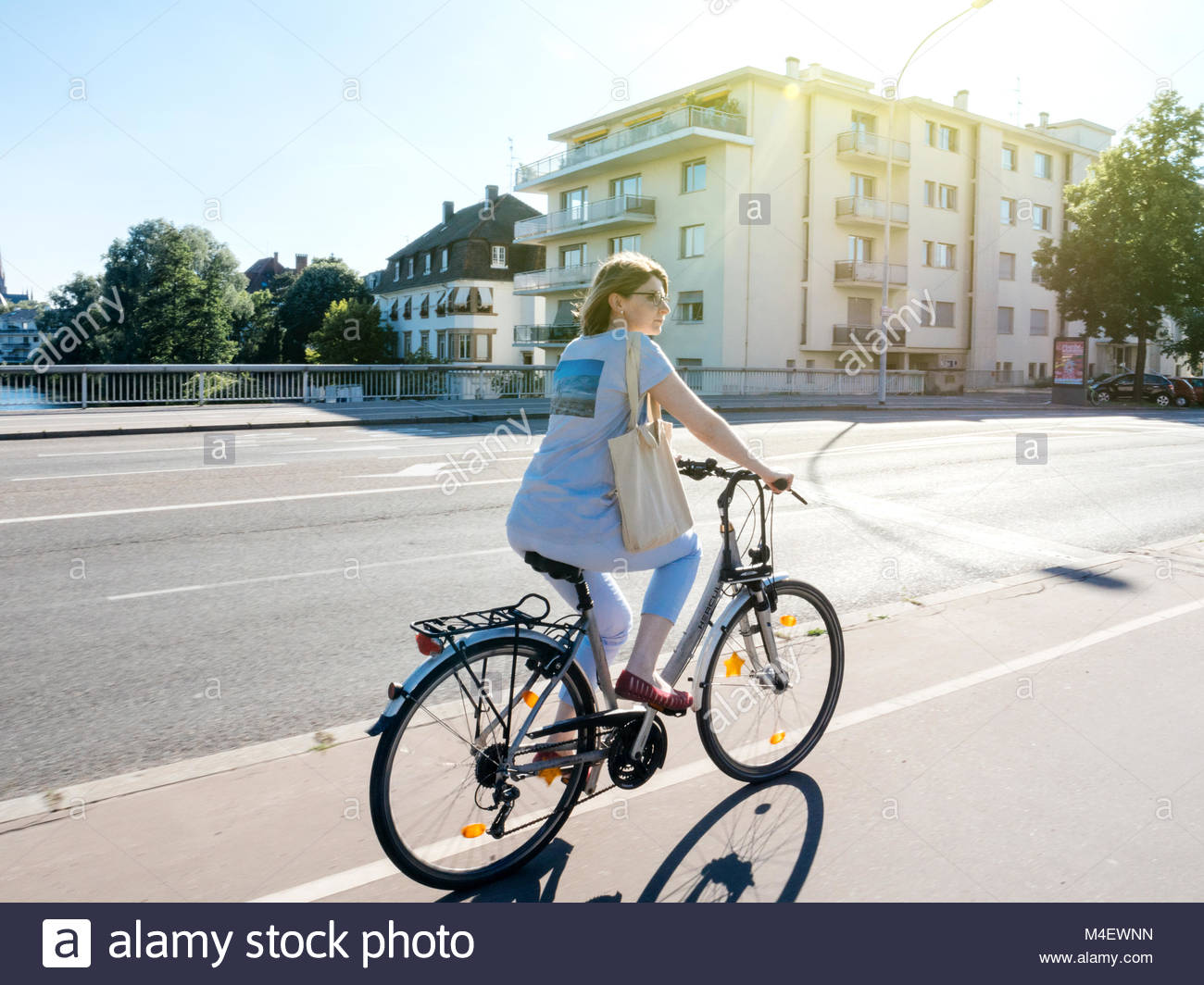 Elegant French woman cycling in Strasbourg, France - Stock Image